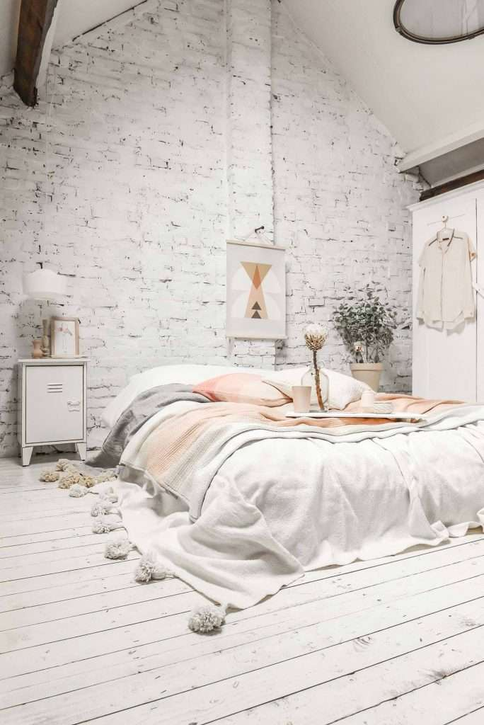 camera da letto bianca con parete grezza